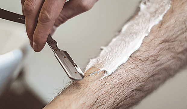 Man shaves his leg with a razor blade, shaving foam on a leg