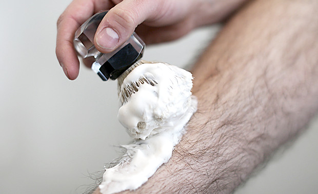Man puts shaving foam with a shaving brush on his leg